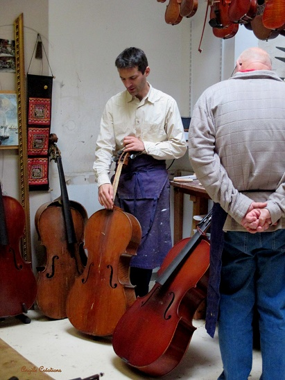Guillaume examinant un violoncelle avec Michel , un passionné en stage!