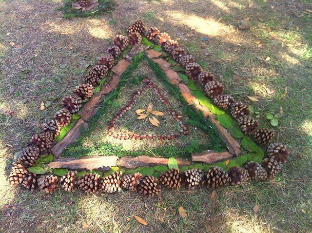 Land'art triangle en pommes de pin et feuillage