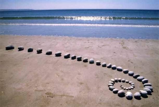 Instllation de galets en courbe sur plage land'art